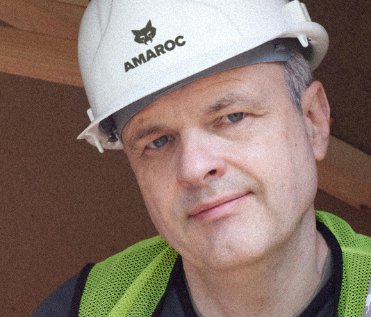 Satisfied builder standing on building site with Amaroc logo printed onto his hardhat